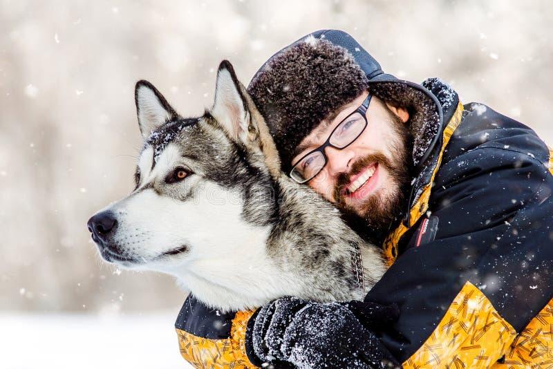 En man med en skägg- och hundmalamute arkivbilder