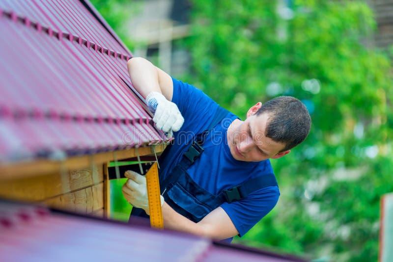 En man med ett hjälpmedel under reparationen av taket royaltyfria foton