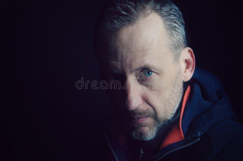 En man med ett skägg i det dunkla ljuset arkivbilder