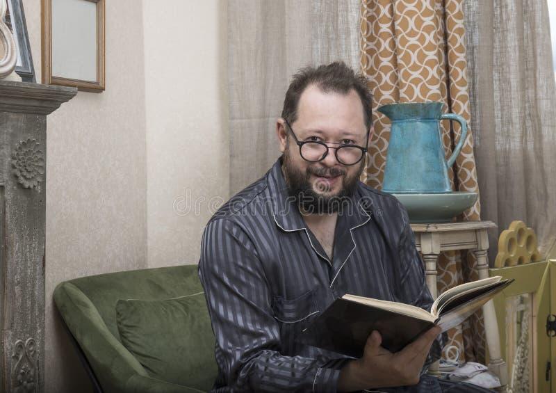 En man med ett skägg i hans pyjamas läser en bok fotografering för bildbyråer