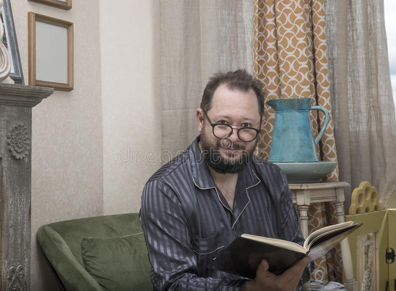 En man med ett skägg i hans pyjamas läser en bok royaltyfria foton