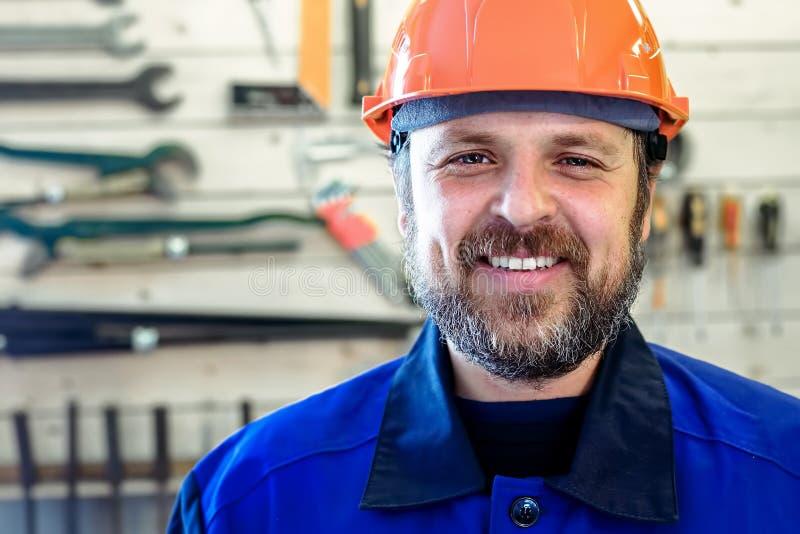En man med ett skägg i en hjälm och arbetskläder ler ett snövitt leende mot bakgrunden av en ställning med hjälpmedel royaltyfria bilder