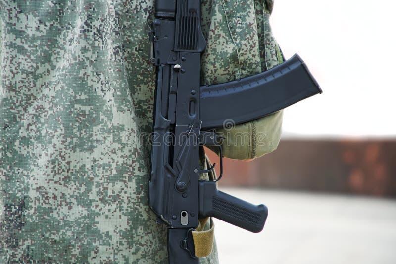 En man med ett vapen i skyddskläder som är kaki- på en vit bakgrund Patrull eller säkerhet Federala skjutvapen licenserar royaltyfri foto