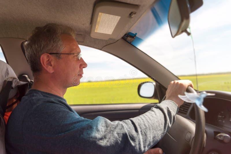 En man med exponeringsglas som kör en bil Chauff?ren k?r bilen arkivfoto