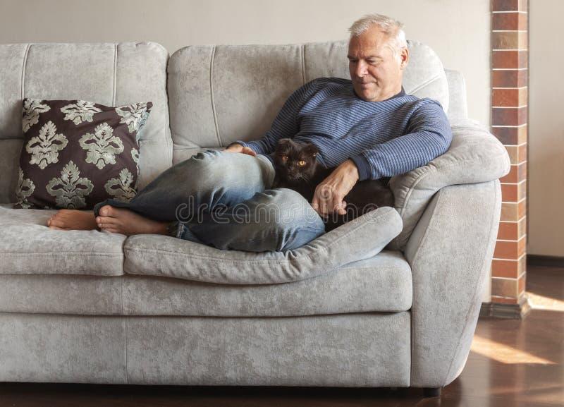 En man med hans katt på soffan royaltyfri foto
