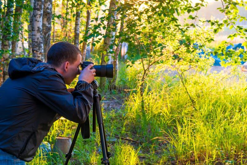 En man med en kamera på en tripod tar bilder arkivbild