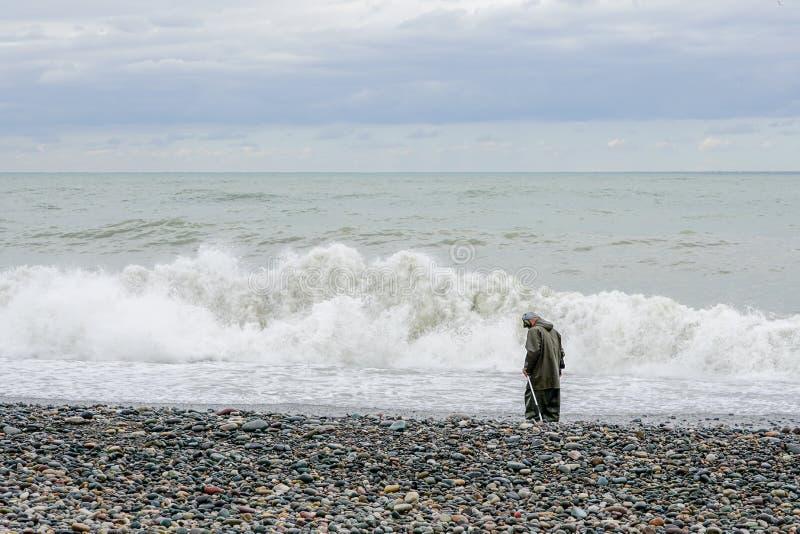 En man med en metalldetektor promenerar stranden av Blacket Sea, skattjägare arkivfoton