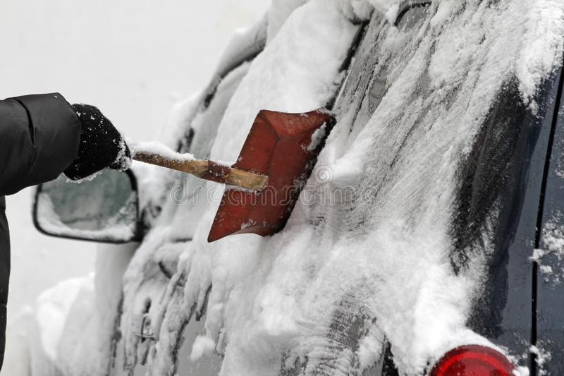 En man med en metallskyffel gör ren bilen från snö på gatan efter stor snöstorm i staden, alla bilar under snö, iskalla vägar, sn arkivfoton