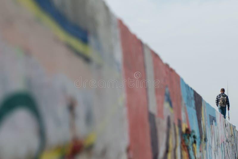 En man med metspöet och ryggsäcken går att fiska att gå på väggen med grafitti royaltyfria foton
