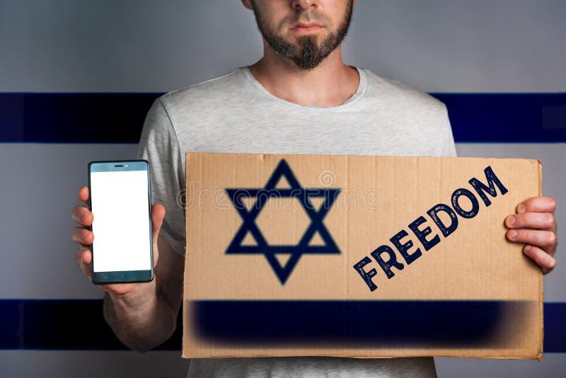 En man med en papp och en telefon i hans hand flaggan av Israel Begrepp av friheter och mänskliga rättigheter Smsa frihet, förlöj royaltyfri bild