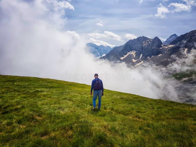 En man med en ryggsäck är på bergssidan mot bakgrunden av moln royaltyfria foton