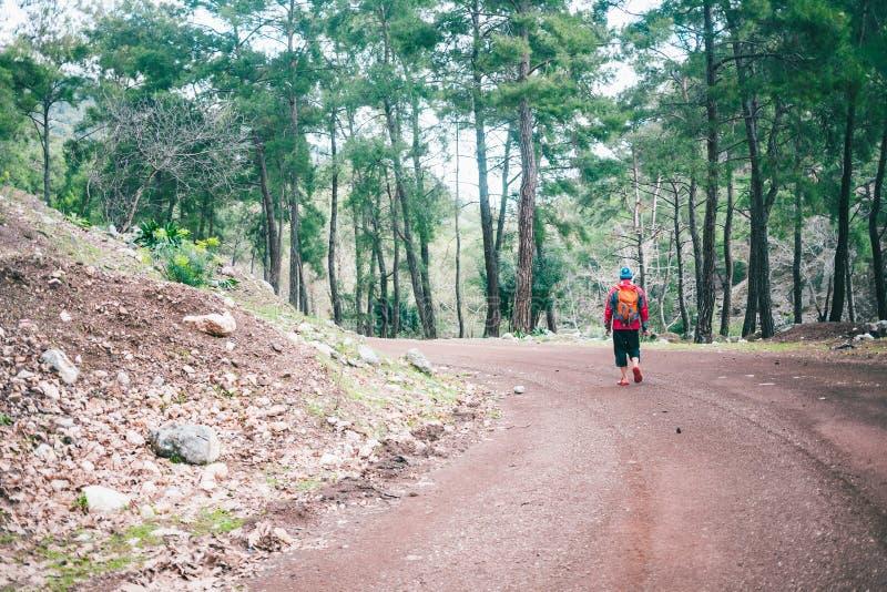 En man med en ryggsäck är på en bergväg arkivfoto