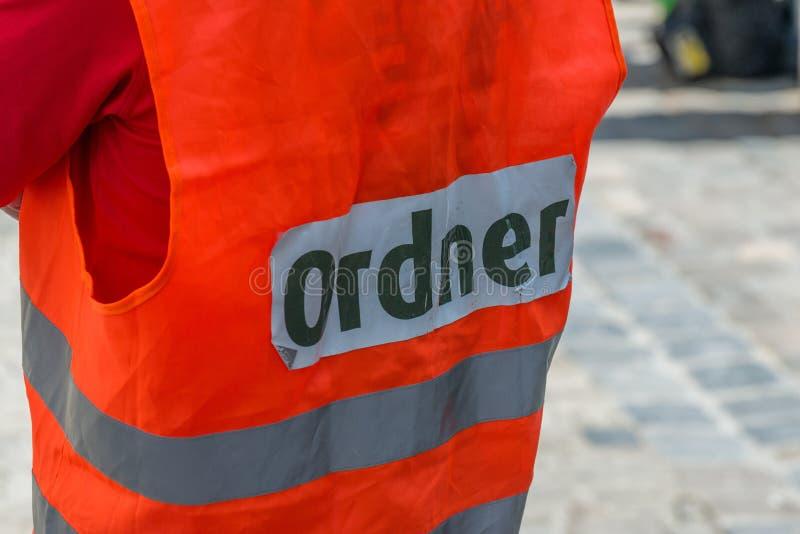 En man med en säkerhetsväst med det tyska ordet - marskalk, Tyskland arkivbild