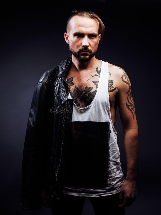 En man med tatueringar på hans armar Kontur av den muskulösa kroppen Ca royaltyfria bilder