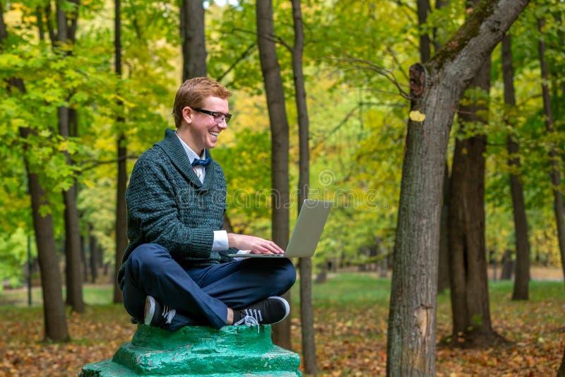 En man med varvöverkanten på en sockel, som låtsar för att vara en staty i hösten, parkerar få idén royaltyfria foton