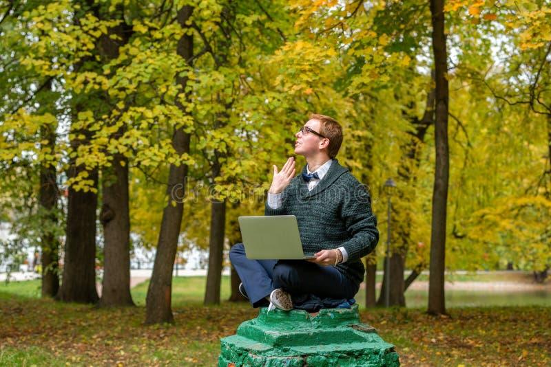 En man med varvöverkanten på en sockel, som låtsar för att vara en staty i hösten, parkerar få idén royaltyfri fotografi