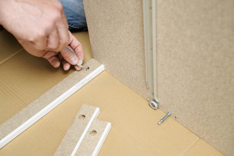 En man monterar möblemanget hemma fotografering för bildbyråer
