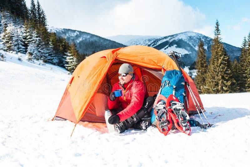 En man nära ett tält i vintern arkivbild