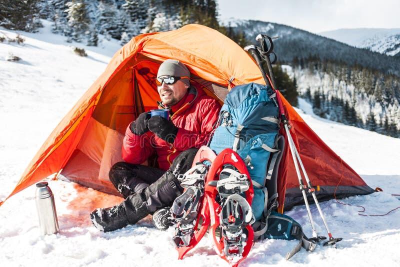 En man nära ett tält i vintern arkivfoto