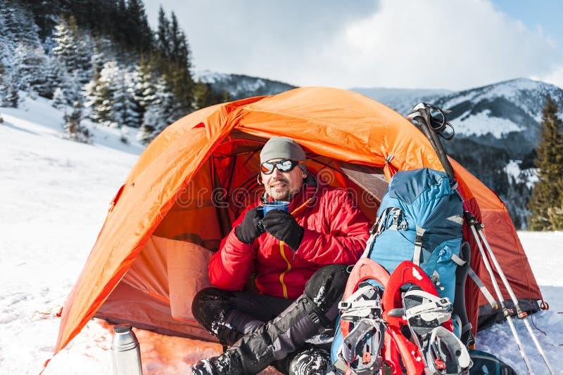 En man nära ett tält i vintern royaltyfri foto