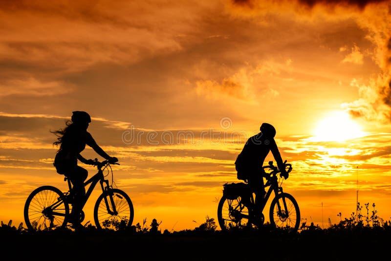 En man och cyklar för en kvinnaritt på vägen med härlig färgrik solnedgånghimmel fotografering för bildbyråer