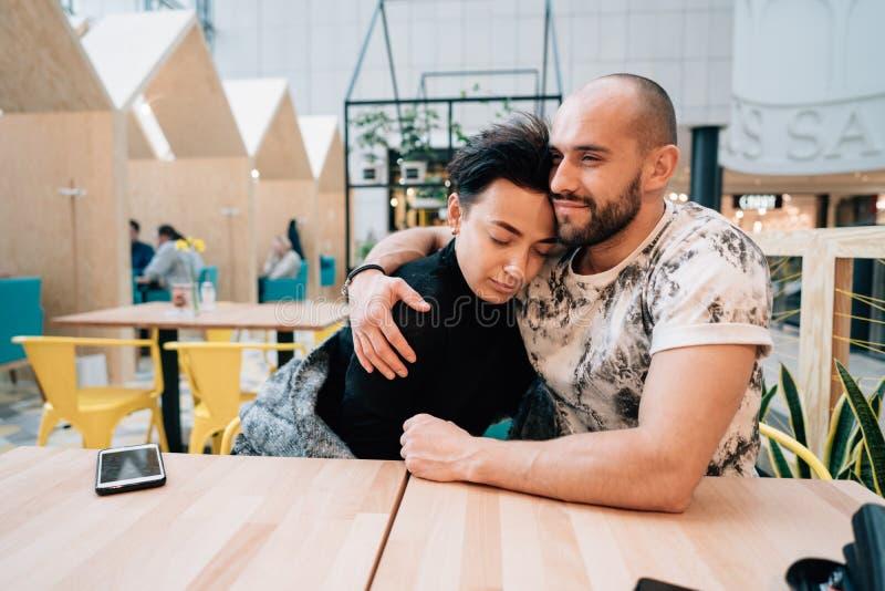 En man och en kvinna sitter i ett kafé arkivbild