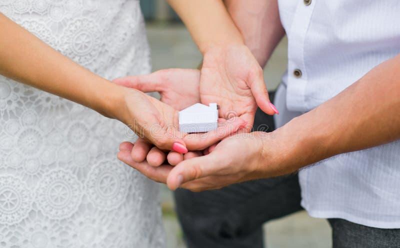 En man och ett kvinnainnehav i deras händer ett litet hus Slut u royaltyfri foto