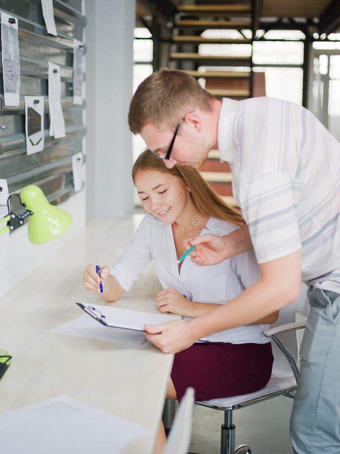 En man och en flicka betraktar ett affärsplan i kontoret royaltyfri foto