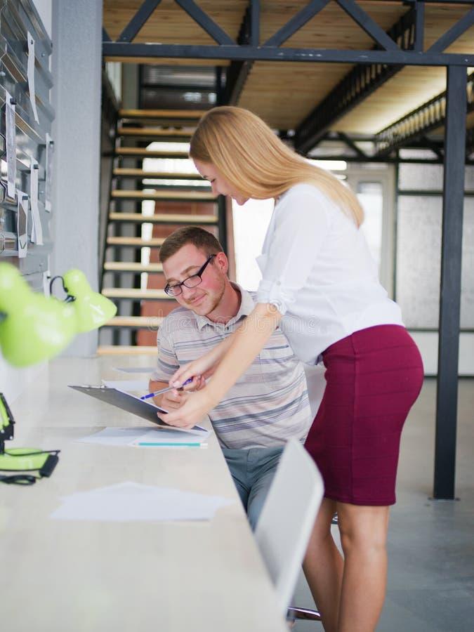 En man och en flicka betraktar ett affärsplan i kontoret arkivfoto