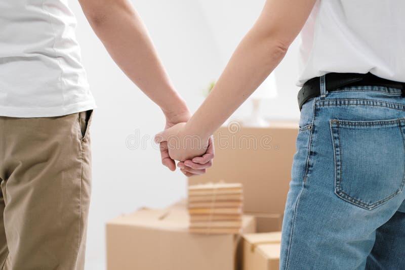 En man och händer för en kvinnahåll, mot en bakgrund av kartonger med saker och en vit bakgrundsnärbild arkivbilder