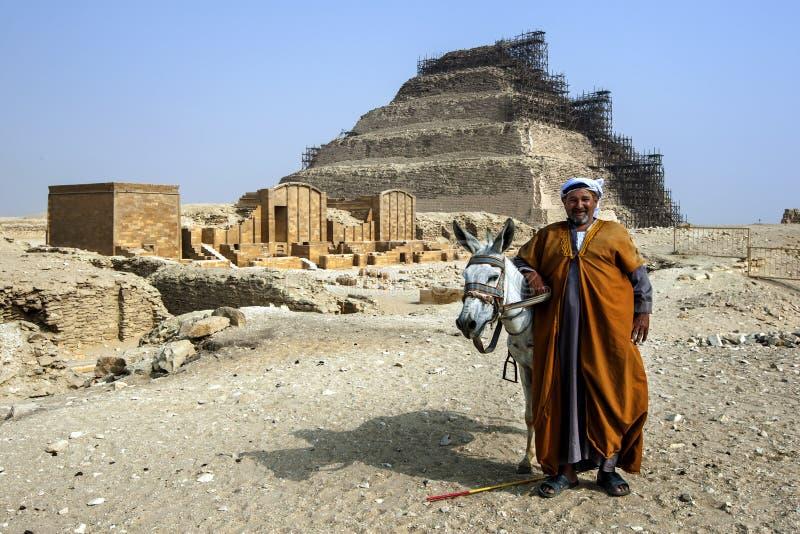 En man och hans åsnaställning framme av momentpyramiden arkivbild