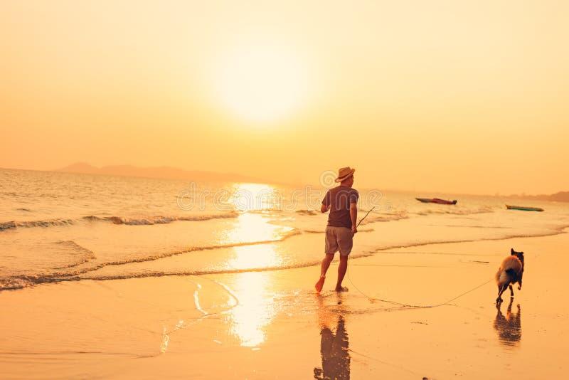En man och en hund som kör på stranden och solnedgången, soluppgång arkivbild