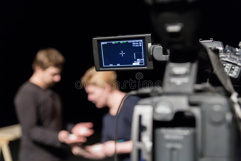 En man och en kvinna i studion som förbereder sig att skjuta Videokamera med LCD-skärm i förgrunden arkivfoto