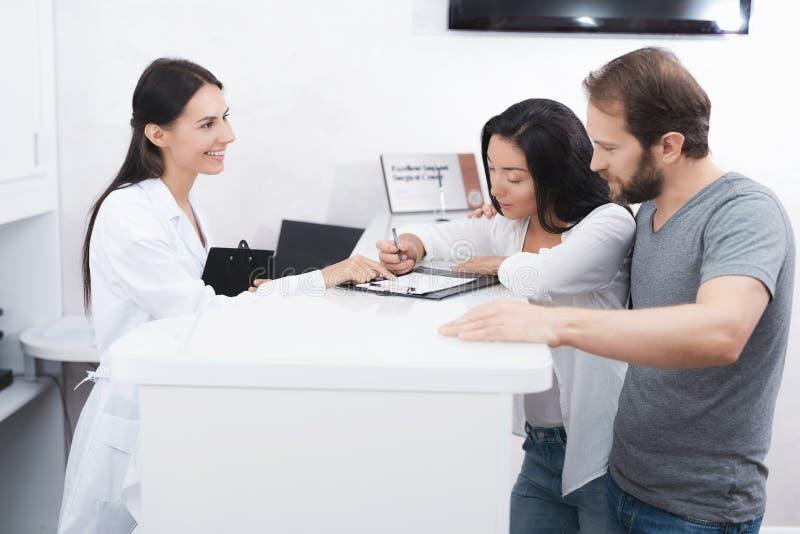 En man och en kvinna kom att se en tandläkare They fylla in den nödvändiga legitimationshandlingar i det väntande rummet royaltyfria foton