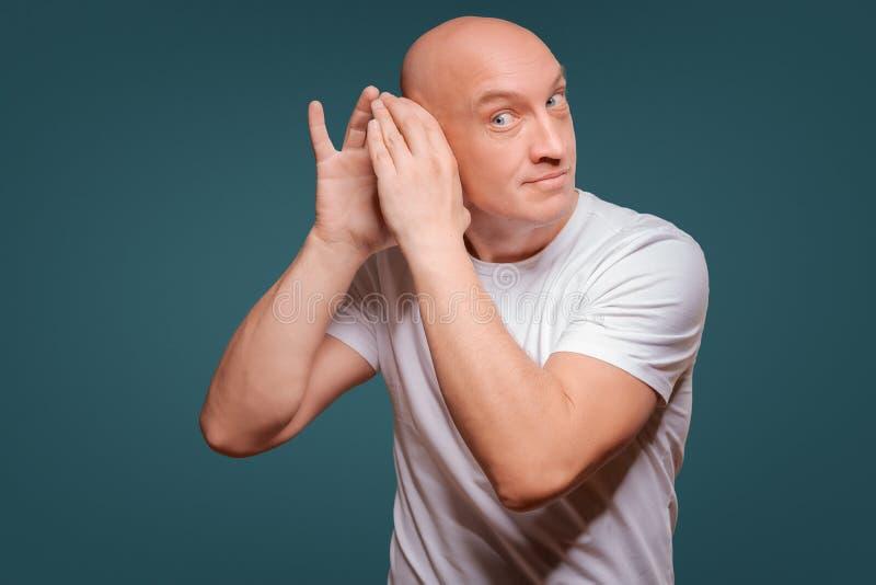 En man på en blå bakgrund, i att rymma hans händer nära hans öra, tjuvlyssnande royaltyfri fotografi