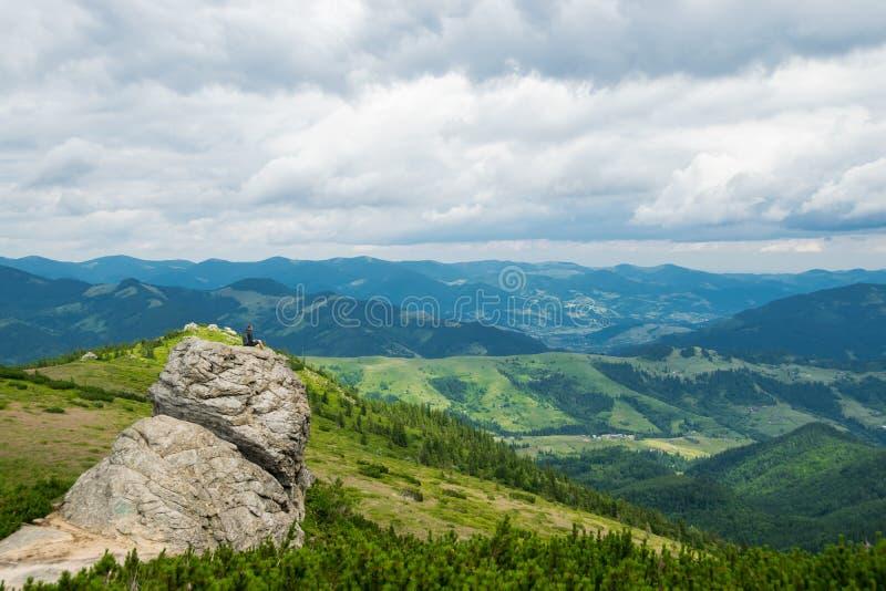 En man på ett klippaöverkant- och berglandskap royaltyfri fotografi