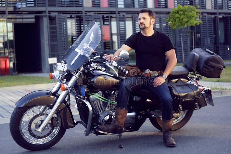 En man på en motorcykel nära kontoret Mannen på en motorcykel tar hans flickvän från arbete Cyklisten kom att arbeta i kontoret _ royaltyfri fotografi