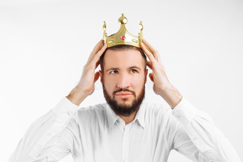 En man på en vit bakgrund, bär en krona på hans huvud, i en fotostudio arkivbilder