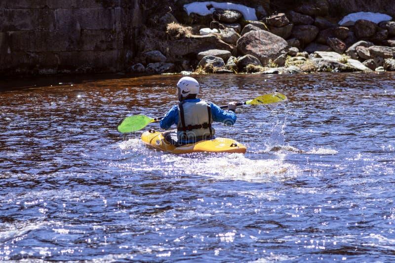 En man p? en bergflod kopplas in, i rafting En flicka kayaking ner en bergflod flicka i en kajak, sidosikt royaltyfria bilder