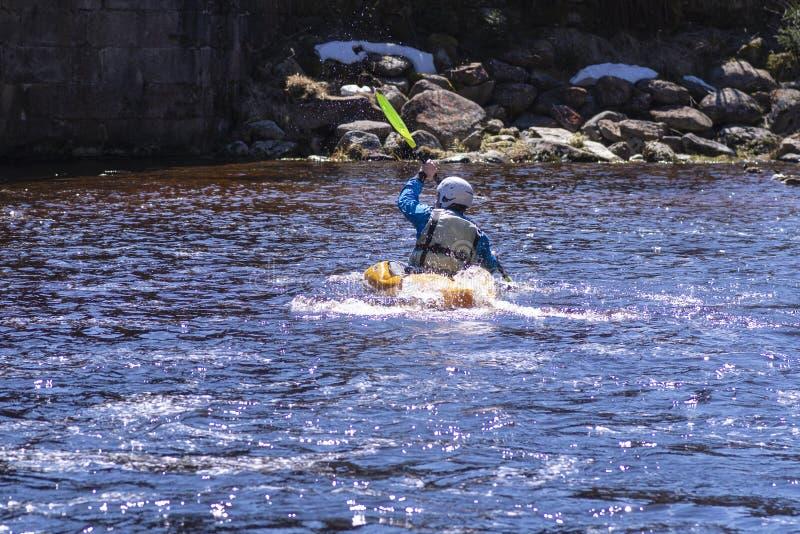 En man p? en bergflod kopplas in, i rafting En flicka kayaking ner en bergflod flicka i en kajak, sidosikt royaltyfri fotografi