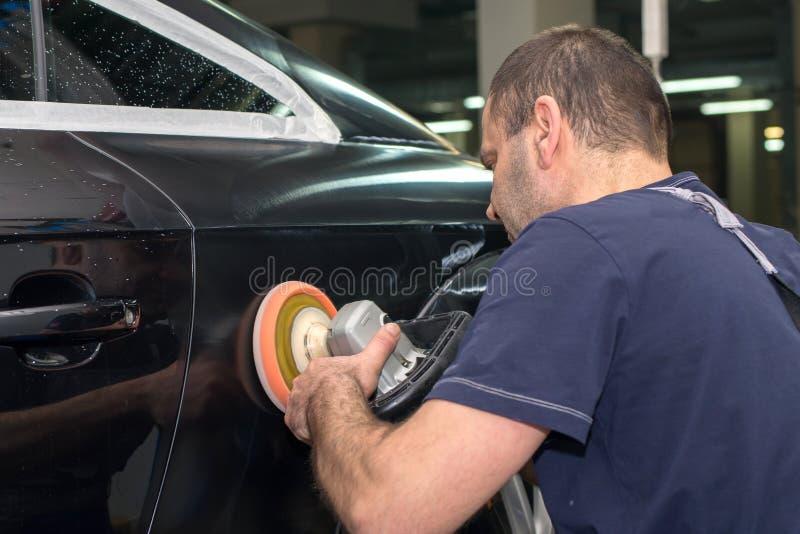 En man polerar en svart bil arkivbild