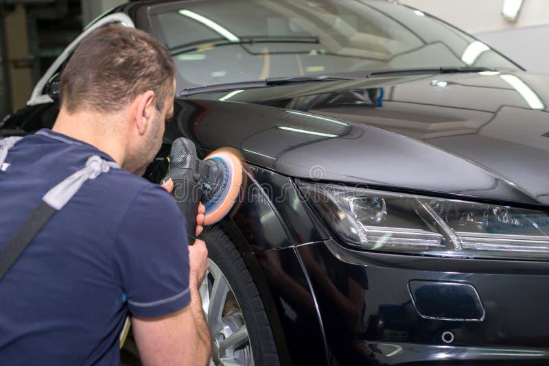 En man polerar en svart bil arkivbilder