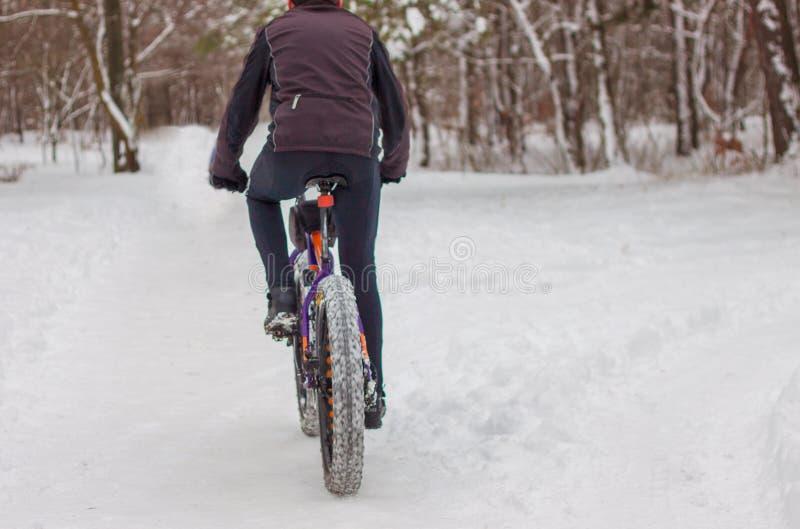 En man rider en cykel i vintern i snön arkivfoton