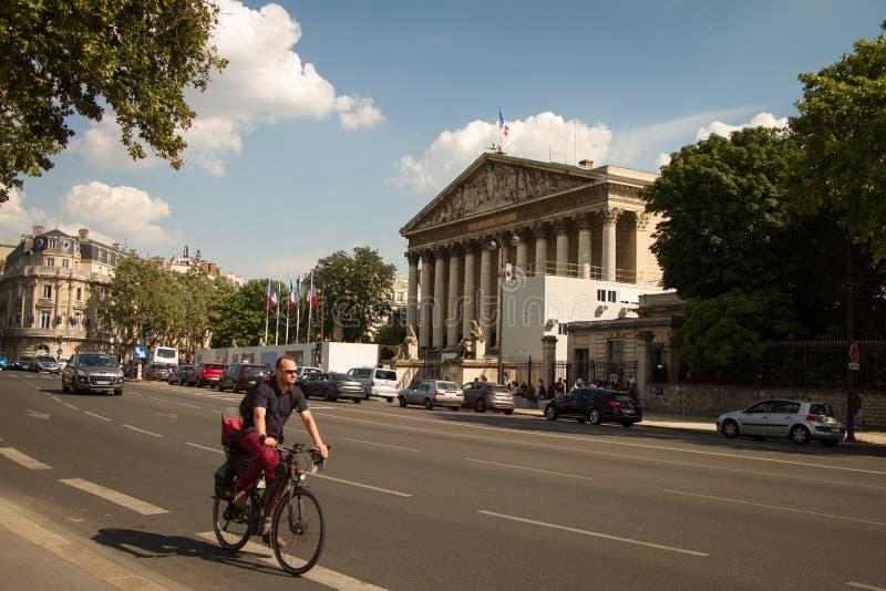 En man rider en cykel längs vägen längs medborgaren Assamley i Paris royaltyfria bilder