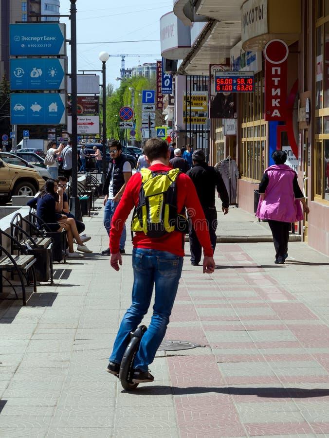 En man rider på en trottoar på en monocycle arkivbilder