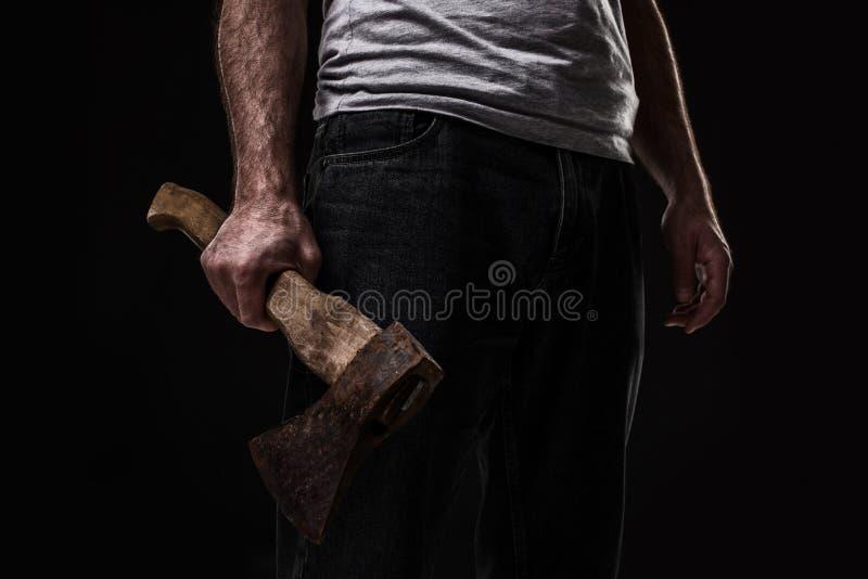 En man rymmer en yxa i hans händer mot på svart bakgrund arkivfoton