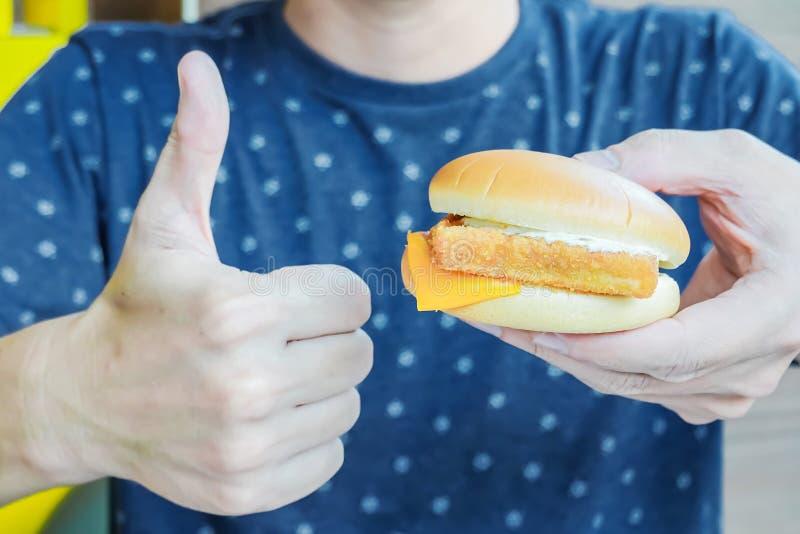 En man rymmer en hamburgare i hans hand och visar upp hans tumme Den så bra unga mannen äter honom den läckra aptitretande fega h fotografering för bildbyråer
