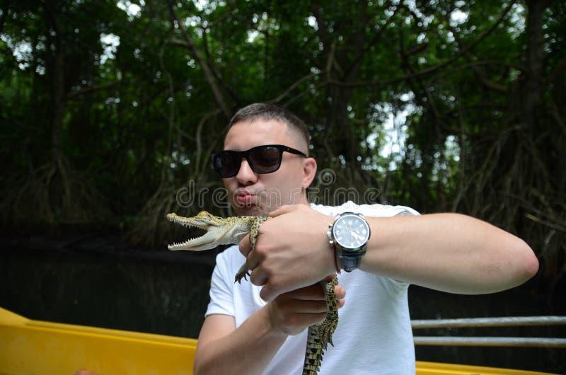 En man rymmer i händer en liten krokodil arkivbilder
