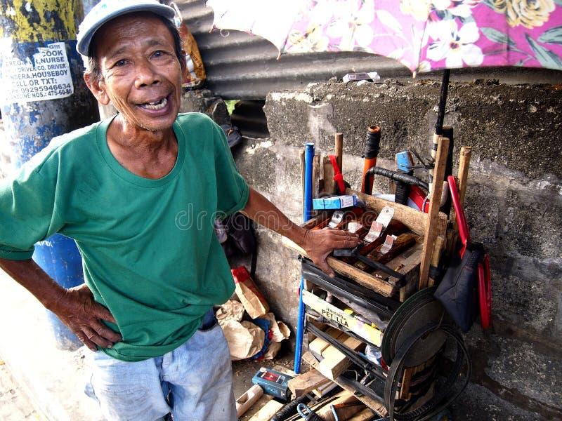 En man säljer en variation av handen - gjorda snickerihjälpmedel längs en gata i den Antipolo staden, Filippinerna royaltyfri foto