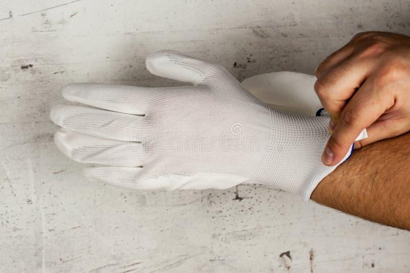 En man sätter på en handske på hans hand för reparationer Hand på ljus konkret bakgrund Bekläda beskådar DIY arkivfoto